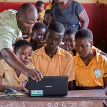 Teacher George Ebo Brown showing children at Archbishop Amissah Junior High School in Western Region how to use a laptop computer. Photo by Ryan Yingling.