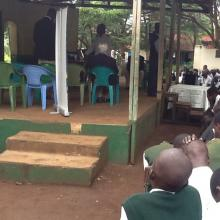 Children taking part in an online inter-school debate. The children are seeing images of the other school on a big screen.