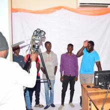 A group of youth testing out cameras in the library.