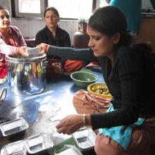 A group of women who learnt business skills at the library fill lunch boxes which the sell, as a small business.