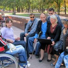 Group of trainees, some in wheelchairs, in the park.
