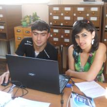 A library trainer shows a young woman trainee how to use a computer to access the internet.