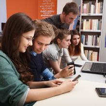 Teenagers using tablet and desktop computers in the library.