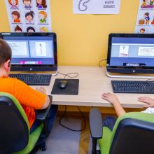 Two children working on computers, learning financial literacy skills, in the library.