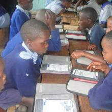 Children in a classroom reading with the e-readers.