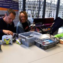Parents and a child learning robotics skills in the library.