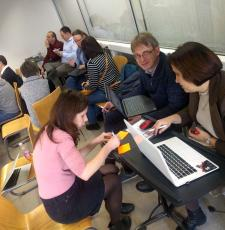 People sitting and working in groups at the open science trainer bootcamp in Debrecen, Hungary.
