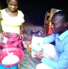 Zariakah Kyozira practising new baking skills at home, watched by Isa Maganda, Isa Maganda, Chief Librarian at Nambi Sseppuuya Community Resource Centre in Uganda.