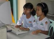 Burmese girls working at a computer.