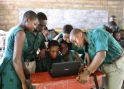 Children in a school classroom crowded around a laptop computer.