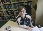 EIFL Copyright Coordinator in Poland, Barbara Szczepańska, sitting at her desk, with bookshelves in the background.