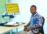 Young man, Gorata Matome, using large print on a computer screen.