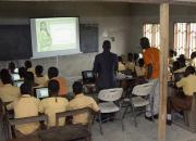 Children learning to use computers in a school classroom in Ghana.