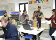 librarians, parents and children with a computer in the maker space