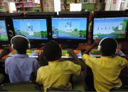 Three children using computers with maths software to practice their maths.