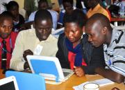 In the photo: three librarians learning computer skills, using a laptop.