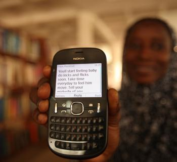 A mother-to-be shows a mobile phone with a text messages advising her about what to expect in pregnancy.