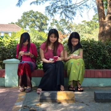 Three young women students from Myanmar using mobile phones to access e-resources.