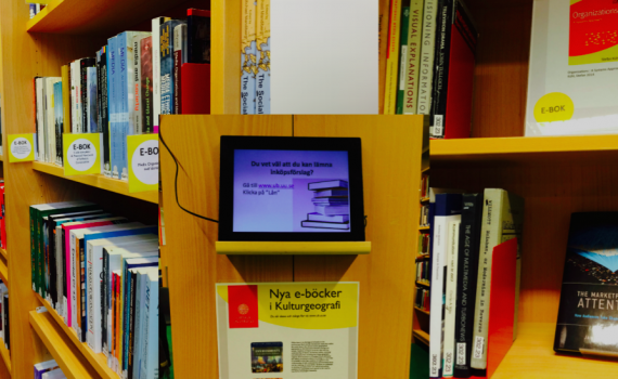 Digital photo frame on the library shelf.