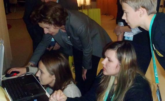 Children show Ms Neelie Kroes how to access and play the game on computers.