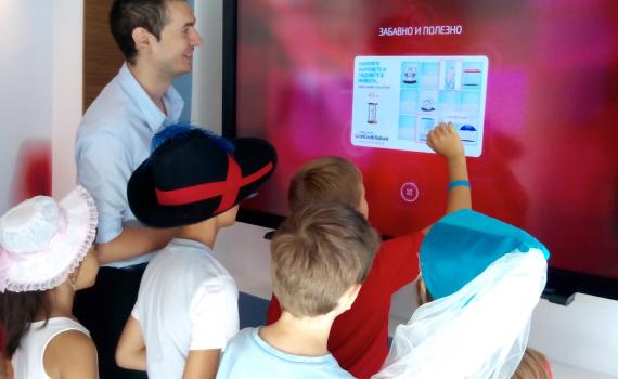 Children in the bank using touchscreen to learn about bank services