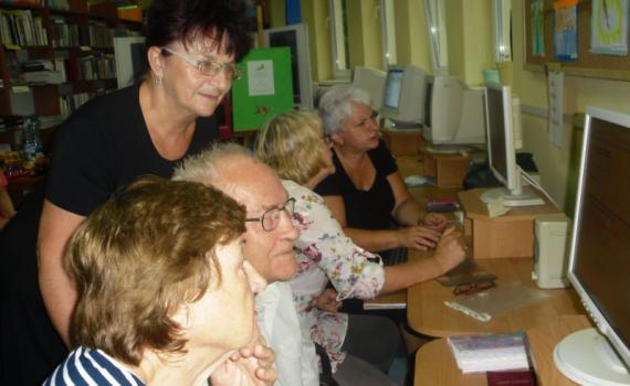 A group of senior people learning internet skills in the library.