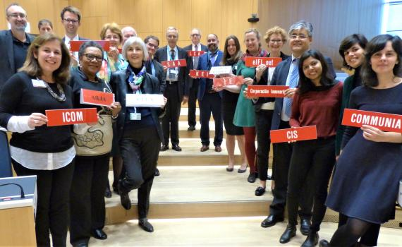 Group photo of 19 representatives from library, archive, museum and education sectors at SCCR/37. They are standing in a long line down a shallow stairs in the WIPO conference hall, holding organization name plaques.