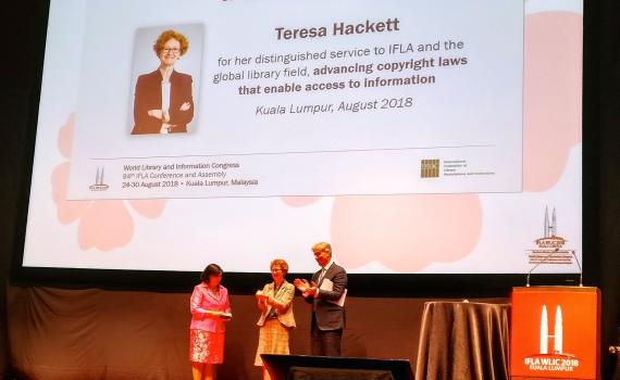 Teresa Hacket receives the award at the IFLA congress. Backdrop is of a banner of Teresa.