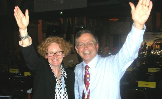 Happy photo of EIFL's Teresa Hackett and Bookshare's Jim Fruchtermann mark adoption of the treaty in Marrakesh, each with an arm raised in celebration.